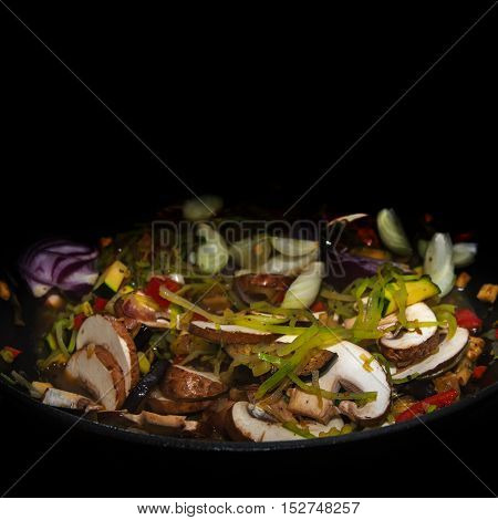 vegetables in a deep pan against a black background with generous copy space selected focus narrow depth of field
