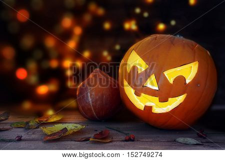 Carved halloween pumpkin with a scary glowing face dark background with blurry lights copy space