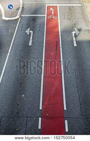 Bicycle lane with red marking and bike symbol on the asphalt road with directional arrows background texture concept for driving school and traffic safety selected focus