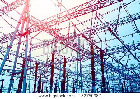 Bottom look up power transmission towers and sun