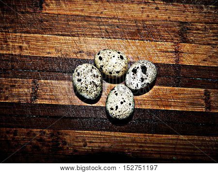 Small specks in the quail eggs are placed on a wooden chopping board