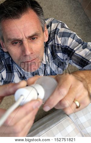 Man Removing An Old-fashioned Inefficient Tungsten Incandescent Light Bulb