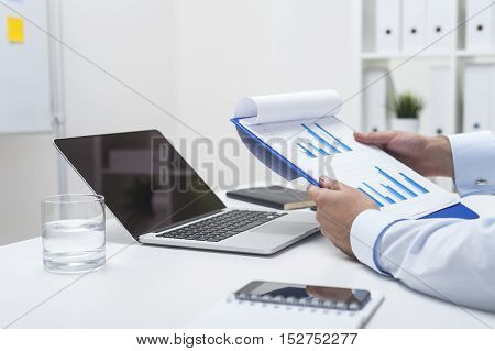 Man Holding Clipboard With Two Blue Graphs