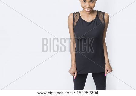 Close up of daring African American girl standing against white wall and looking at the viewer. Mockup