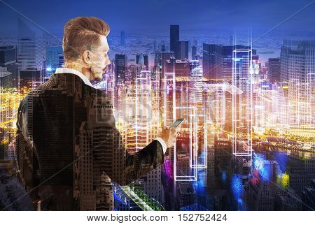 Rear view of bearded businessman on his phone standing against large cityscape at night. Double exposure. Toned image