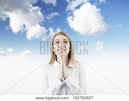 Hoping woman is standing against sky background with her palms together and looking upwards. Concept of prayer. Mock up