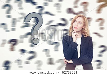 Beautiful businesswoman with red hair is standing against white background. Blurred question marks are falling from the sky. Concept of looking for solution