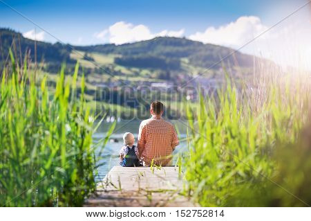 Father With His Son Sitting On Jetty And Enjoying The View On The Sea And Swiss Alps, Switzerland