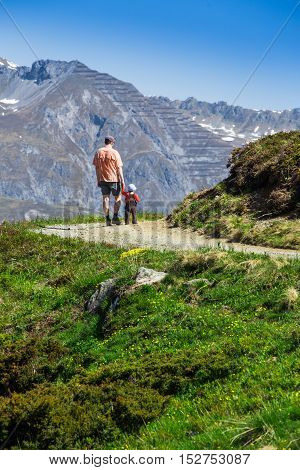 Father With His Son Hiking In Swiss Alps, Madrisa Mountain, Davos, Switzerland