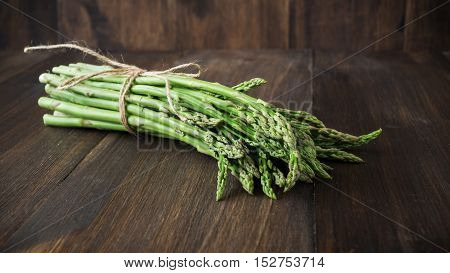 Bundle of pencil thin green asparagus on wooden background selective focus toned horizontal