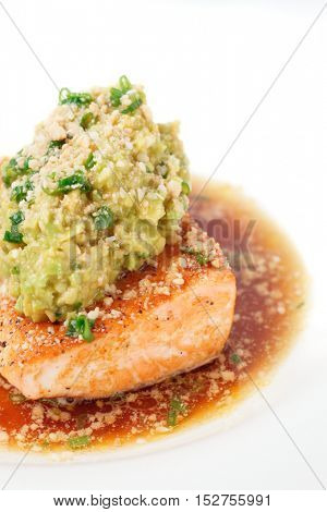 Grilled salmon fillet with avocado mash and savory sauce
