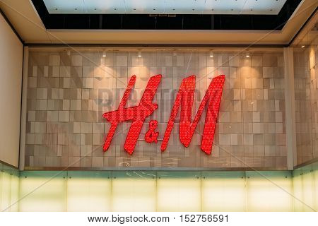 Vilnius, Lithuania - July 08, 2016: Close The Illuminated Red Logotype H M Of Hennes and Mauritz Brand At The Gray Wall Of Store In Acropolis Shopping Center.