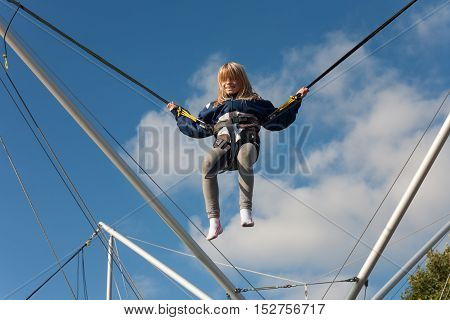 Little girl enjoying jumping with trampoline jumping rope