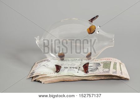 Glass piggy bank with Indian Currency Rupee bank notes on gray background