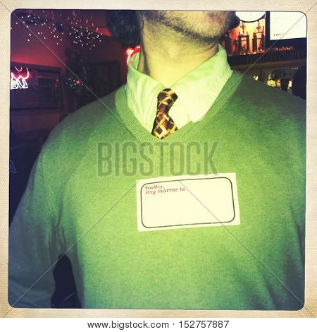 close filtered image of a man in a sweater and tie with a Hello, My Name Is name tag