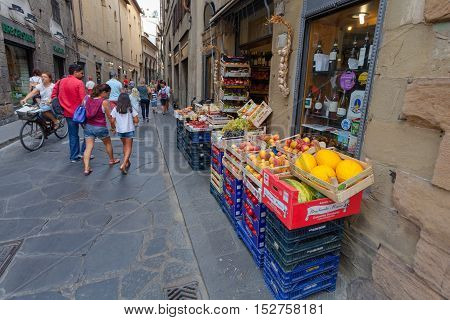 Florence ITALY- September 10 2016: The boxes and baskets of store (outdoor Fruit Shop Greengrocery) with fresh and ripe fruits and vegetables on the narrow street of Florence, Italy.