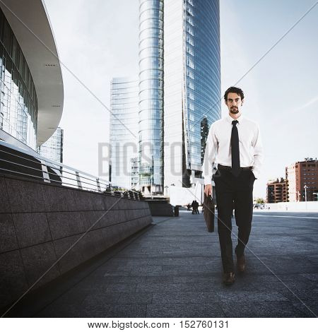 Businessman walking on the street with skyscraper background