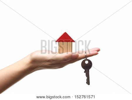 Female hand holding a house and a key / Buying a new house concept
