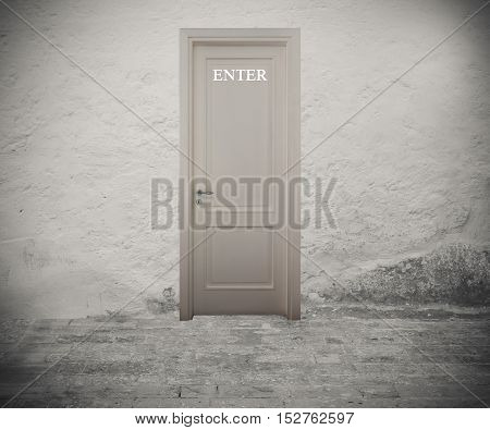 Written enter on the white door with wall background