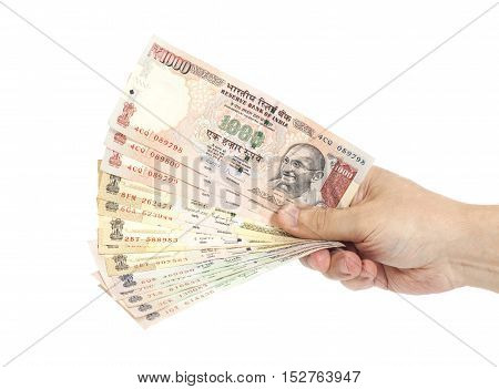 Hand with Indian thousand rupee notes isolated