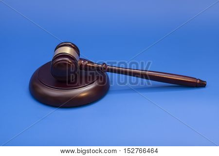 Wooden judge gavel and soundboard isolated on blue background