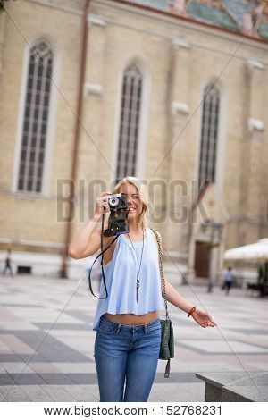 Young tourist girl holding a retro camera in the city.