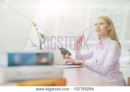 Cute female student is studying in library. She is sitting at desk near books and typing on a laptop. The woman is thinking and smiling