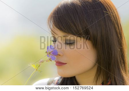 Beautiful meditative girl sniffing a flower. The young woman is enjoying the natural beauty. Wonderful picture with nice colors.