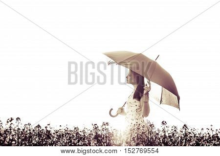 Beautiful eyes closed art woman with umbrella in meadow . The picture is digitally altered for an artificial style.