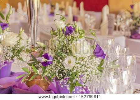 Premium dinner gala table with napkins glasses and flowers. High class arrangement for e.g. a wedding birthday or business meeting.