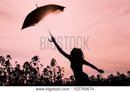 Unplugged silhouette woman with red umbrella and wanderlust. Perfect warm scene with girl want to fly. Showing the power of imagination and departure to new horizons like climate change or mindfulness.