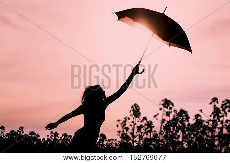 Unplugged free silhouette woman with umbrella fly to future. Perfect warm scene with girl want to fly. Showing the power of imagination and departure to new horizons like climate change or mindfulness.