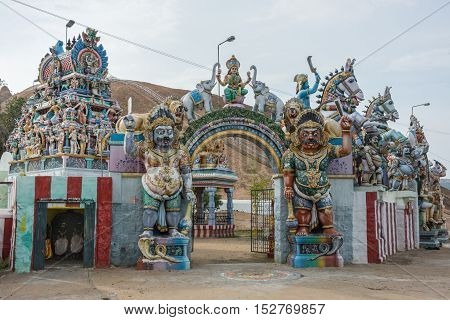 Madurai India - October 21 2013: Two copies of Karuappan Sami guard the entrance to their shrine. Lakshmi is present on top of the gate. Horses strong men Vimanam of sanctuary and more statues.