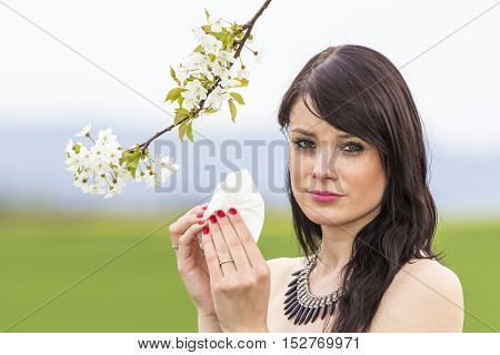 Sad hayfever girl in spring nature with blossom branch season. The beautiful young woman is pained by her allergy every year. She holds a tissue in her hands.
