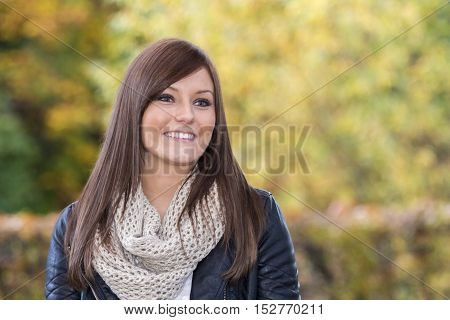 Beautiful woman with a wonderful smile. Portrait of an attractive young adult at a european park in autumn. With a nice colorful background and copy space.