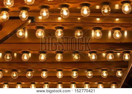 Many light bulbs shining bright. Plenty lightbulbs in rows on ceiling burn.