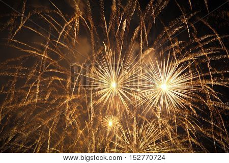 Fantastic pyrotechnics fireworks with golden stars in black sky. Premium magic firework show at e.g. New Year's Eve Independence Day or wedding celebration.