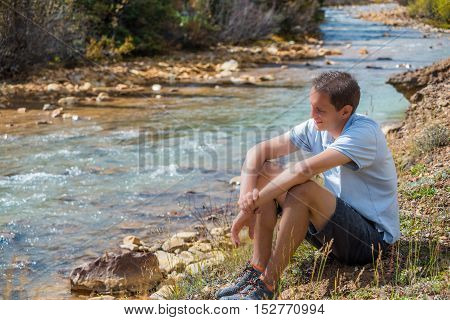 Mineral Creek stream in Colorado, USA by Silverton during the fall and smiling man sitting looking over river