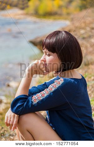 Young woman sitting contemplating by light green creek during autumn with hand on face