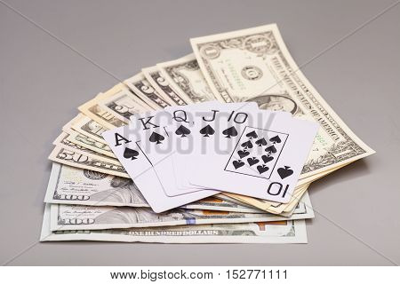 royal flush playing cards and dollars isolated on gray background