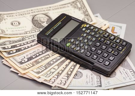 calculator on dollars isolated on gray background