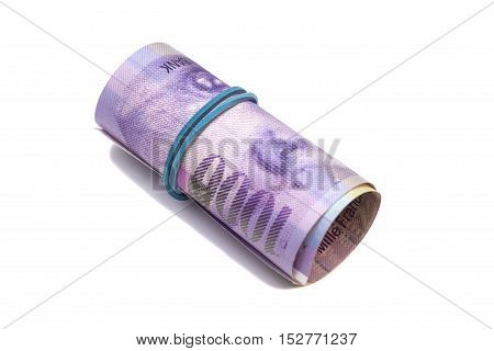 Swiss thousand francs in a roll on white background