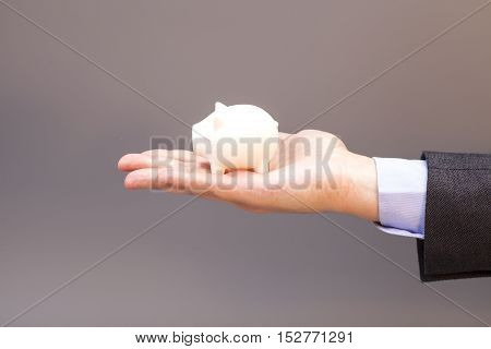 piggy bank on man hand isolated on gray