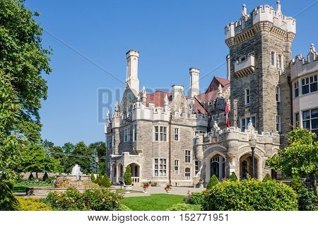 Toronto, Canada - July 22, 2014: Casa Loma gothic castle and museum with fountain and canadian flag