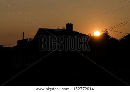 Sunset with silhouette of residential suburban home