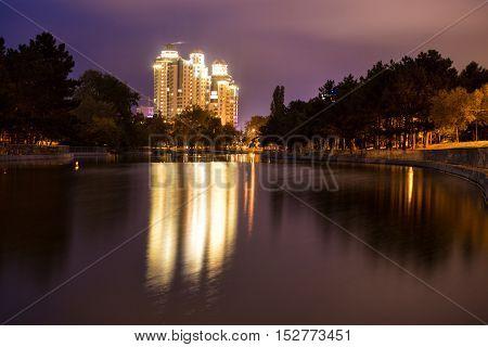 Odessa Ukraine. Night park view. Light of skyscraper is reflected in water.