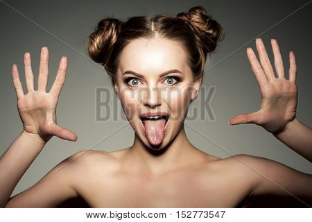 Emotional girl. Beautiful modern model shows tongue Positive woman hipster. Emotions on face. Hands up