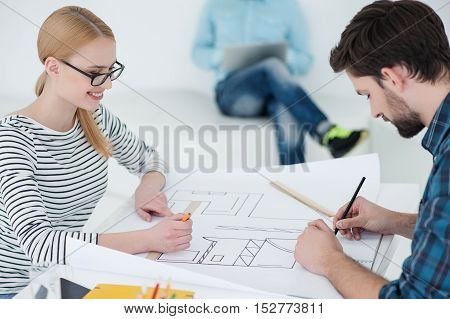There needs completion. Close up of young architects discussing blueprint of building, sitting at office with their colleague working in background