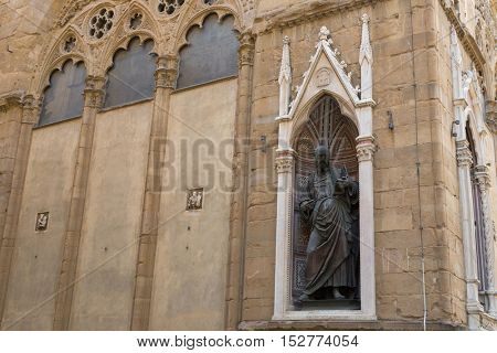FLORENCE, ITALY - SEPTEMBER 2016 : Bronze statue of St. John the Evangelist, detail of Orsanmichele church exterior with 1of 14 external niche figures in Florence, Italy on September 21, 2016.