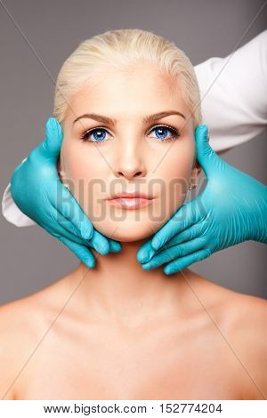 Beautiful face of young woman for Aesthetics facial skincare concept touched by cosmetic plastic surgeon beautician.